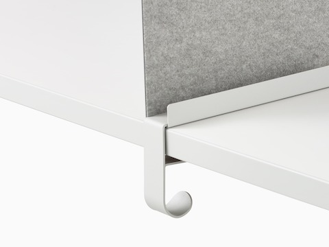 Close up image of a grey OE1 Boundary Screen bag hook attached to a white surface, viewed from an angle.
