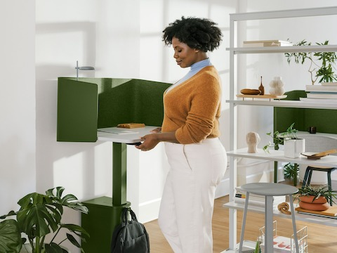A woman standing at a green, single OE1 Micro Pack with a grey OE1 Agile Wall with full shelves and a green OE1 Nook in the background.