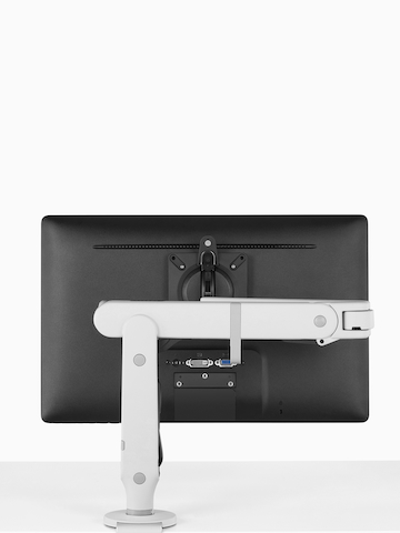 An adjustable Ollin Monitor Arm attached to a work surface. Select to go to the Ollin Monitor Arms product page.