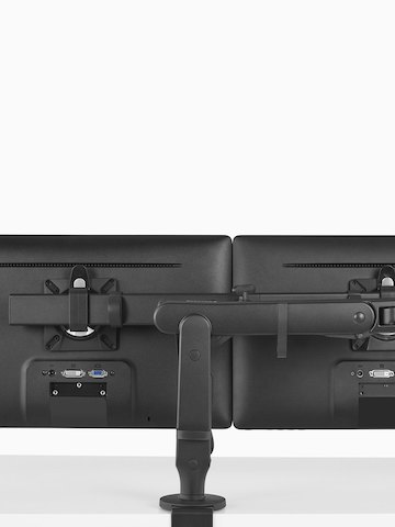 The back view of a black Ollin Monitor Arm supporting two monitors above a work surface. Select to go to the Ollin Dual product page.