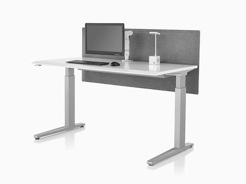 An Ollin Monitor Arm elevates a monitor off the surface of a sit-to-stand table that also supports a Cubert Personal Light.