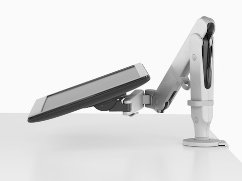Profile view of an adjustable Ollin Monitor Arm supporting a monitor at an extremely low angle.