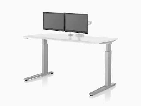 Two Ollin Monitor Arms, one connected to a Flo Power Hub, elevate a pair of monitors off the surface of a sit-to-stand table.