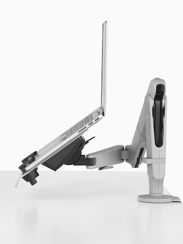An adjustable Ollin Monitor Arm supports an open laptop computer.