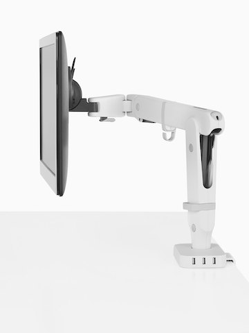 Profile view of a monitor supported by an Ollin Monitor Arm that's connected to  a Flo Power Hub with three USB ports.