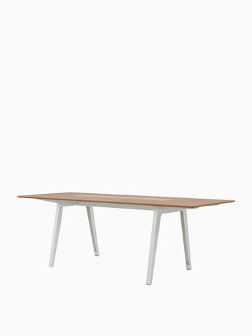An Optimis contemporary meeting table with a white frame and a laminate top in a medium wood finish, viewed at an angle.  Select to go to the Optimis Desking System product page.