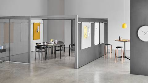 A semi-enclosed Overlay room with two entryways, gray perforated metal exteriors, and markerboard interiors with a table and six chairs inside.