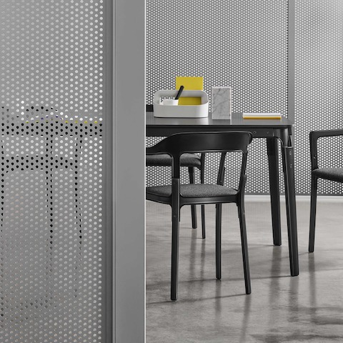 A close-up of a semi-enclosed Overlay room with gray perforated metal walls with a black conference table and four chairs inside.