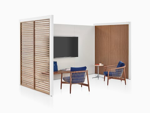 A three-sided Overlay space with walnut wood slats, walnut laminate, and gray tackable fabric with two chairs, a bench, and a monitor inside.