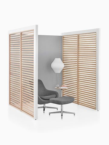 A three-sided Overlay space with birch wood slat side walls and gray fabric back wall with a lounge chair and side table inside.