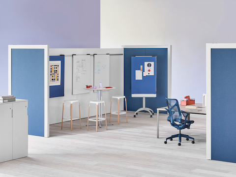 Two Overlay room dividers placed across each other with tables and chairs in between with markerboards in the interior and dark blue fabric on the exterior.