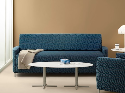 A blue Pamona Flop Sofa and complementary chair in a healthcare lounge.