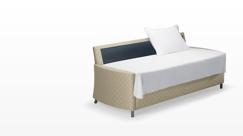 A beige-patterned Pamona Flop Sofa converted into a sleep surface with a sheet and pillow.