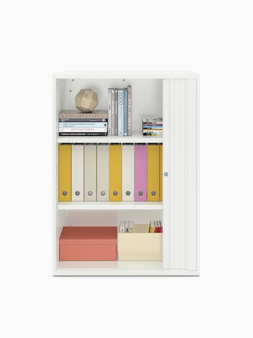 Books and binders fill a partially open Paragraph Storage unit with three modules and a tambour door, viewed from the front.