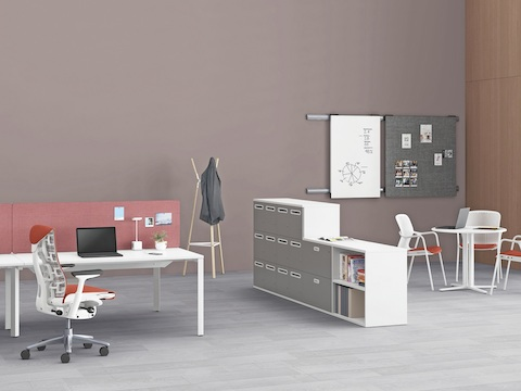 A Paragraph Storage unit divides space in an open office, separating Layout Studio benching from a round Everywhere Table for quick collaboration.