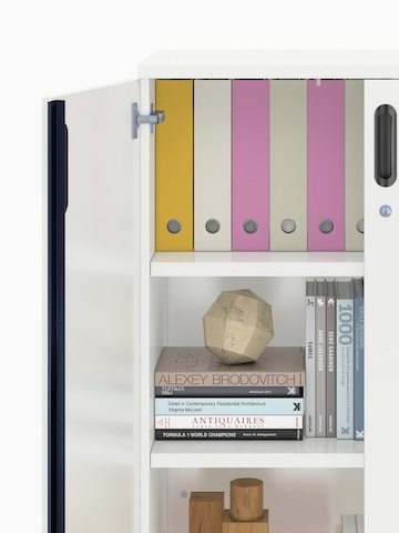 Partial view of a Paragraph Storage unit, focusing on an open hinged door and the books and binders inside.
