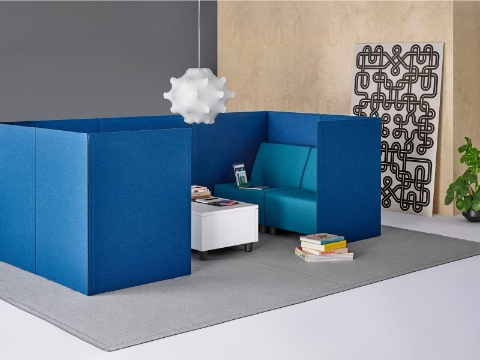 Blue freestanding Pari Screens define the boundaries of a small meeting area or solo work zone containing soft seating.