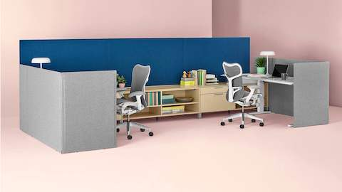 Gray freestanding Pari Screens combine with blue surface-attached Pari Screens to create boundaries for adjacent workstations.
