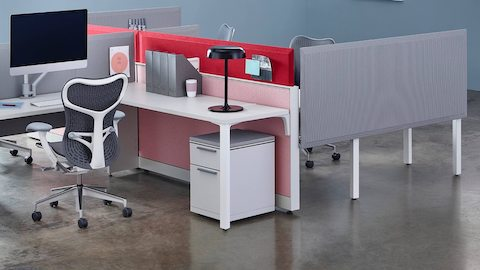 Surface-attached and frame-attached Pari Screens in shades of gray, pink, and red create boundaries in an open work area.