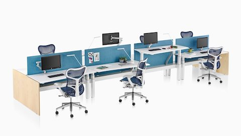 Two runs of Renew Link sit-to-stand work surfaces separated by blue Pari Screens and served by blue Mirra 2 Chairs.