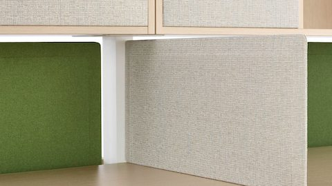 A light gray Pari Screen provides privacy by attaching to the seam between adjacent work surfaces.