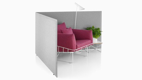 Light gray Pari freestanding screens provide the boundary for a sitting area featuring a Wireframe Sofa in a soft red shade.