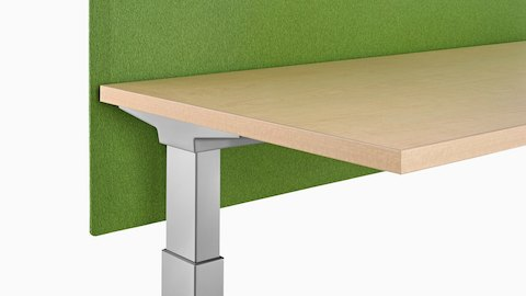 Close view of a green surface-attached Pari Screen affixed to a height-adjustable work surface.