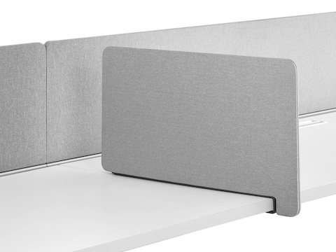 A gray fabric rectangular Personal Side Screen attached to a Layout Studio bench with a gray, flat-edge fabric, center privacy screen.