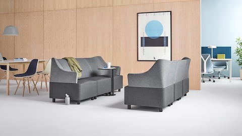Plex modular elements form two gray sofas facing each other in an informal collaboration setting.