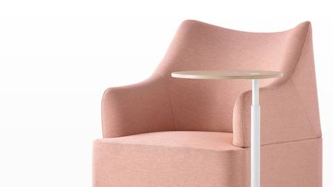 Close angled view of the sculptured back on a salmon Plex club chair paired with a height-adjustable work table.