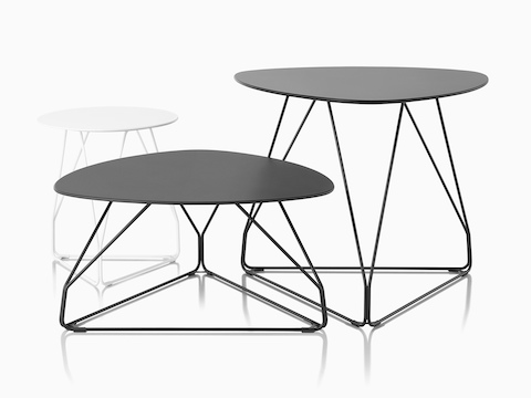 Three Polygon Wire occasional tables. One is white with a round top and the other two are black with rounded triangular tops.