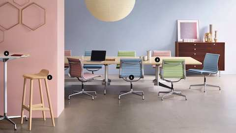 A group of colorful Eames Aluminum Group Side Chairs arranged around a large Eames Table in a Meeting Space. Highlighting the materials and finishes shown.