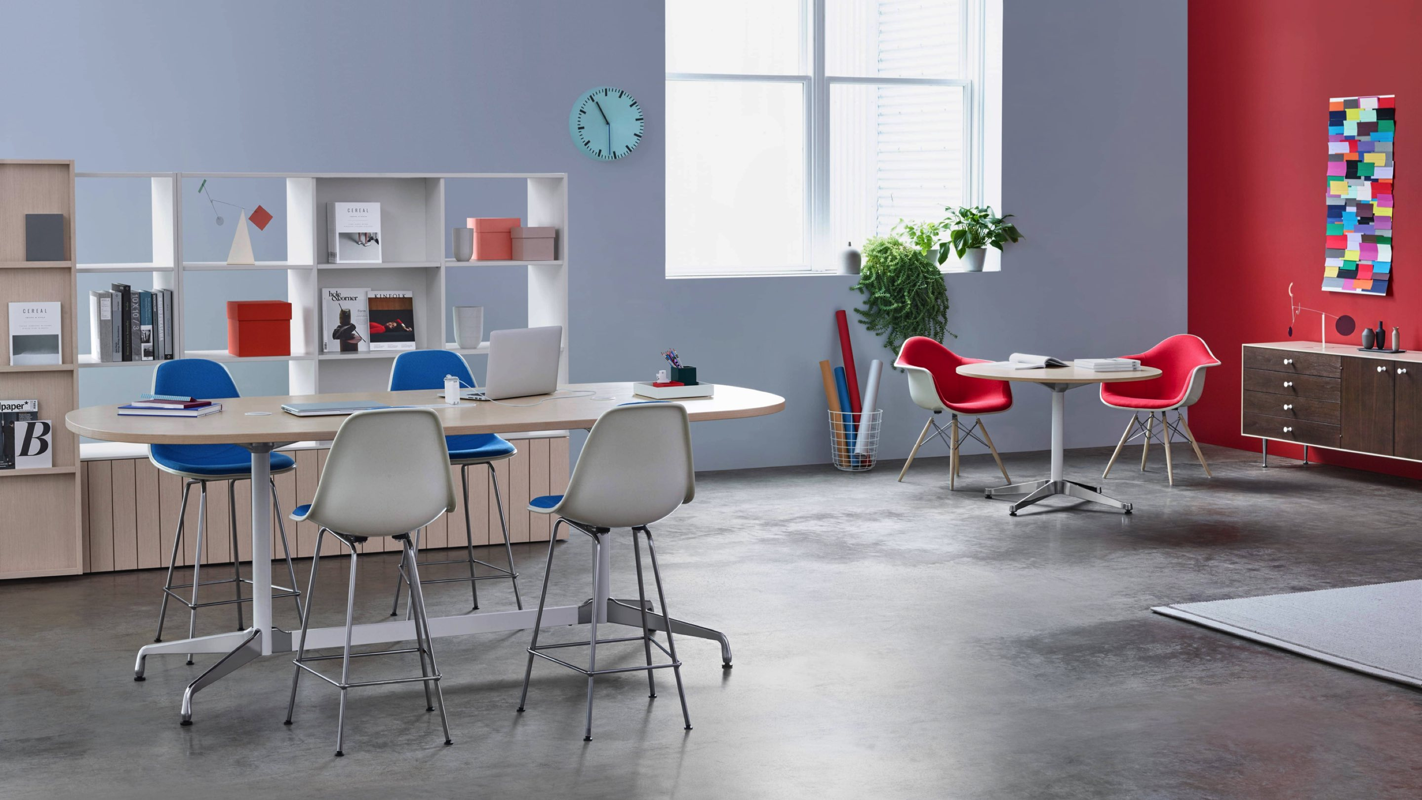 This Workshop setting is built around a group of four Eames Stools around a standing-height Eames Table, with a pair of upholstered Eames Molded Fiberglass Armchairs at a small Eames Table below a nearby window.