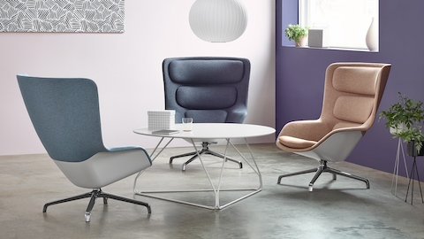 A sitting area featuring three Striad lounge chairs in shades of blue and beige around a Polygon Wire Table.