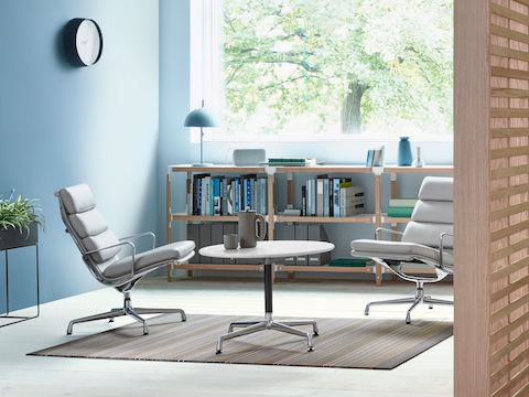 A lounge space featuring two white Eames Soft Pad Chairs. Select to go to the seating page for the Herman Miller Collection.