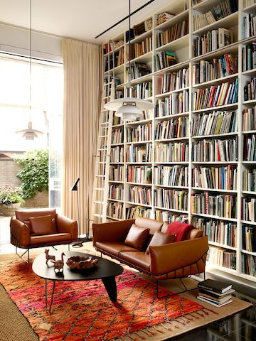 A Noguchi Rudder Table with a walnut finish surrounded by a Wireframe two-cushion sofa and chair and a wall of books.