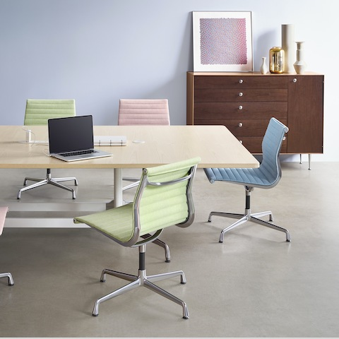 A group of colorful Eames Aluminum Group Side Chairs arranged around a large Eames Table in a Meeting Space.