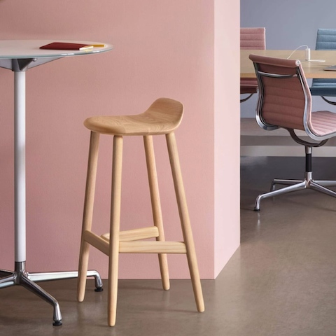 A Crosshatch Stool and Eames standing-height table. The background features a group of colorful Eames Aluminum Group side chairs around a large Eames Table.