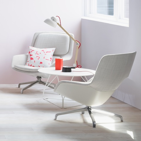 Two Striad Lounge Chairs face each other on either side of a Polygon Wire Table, in a casual brightly lit setting.