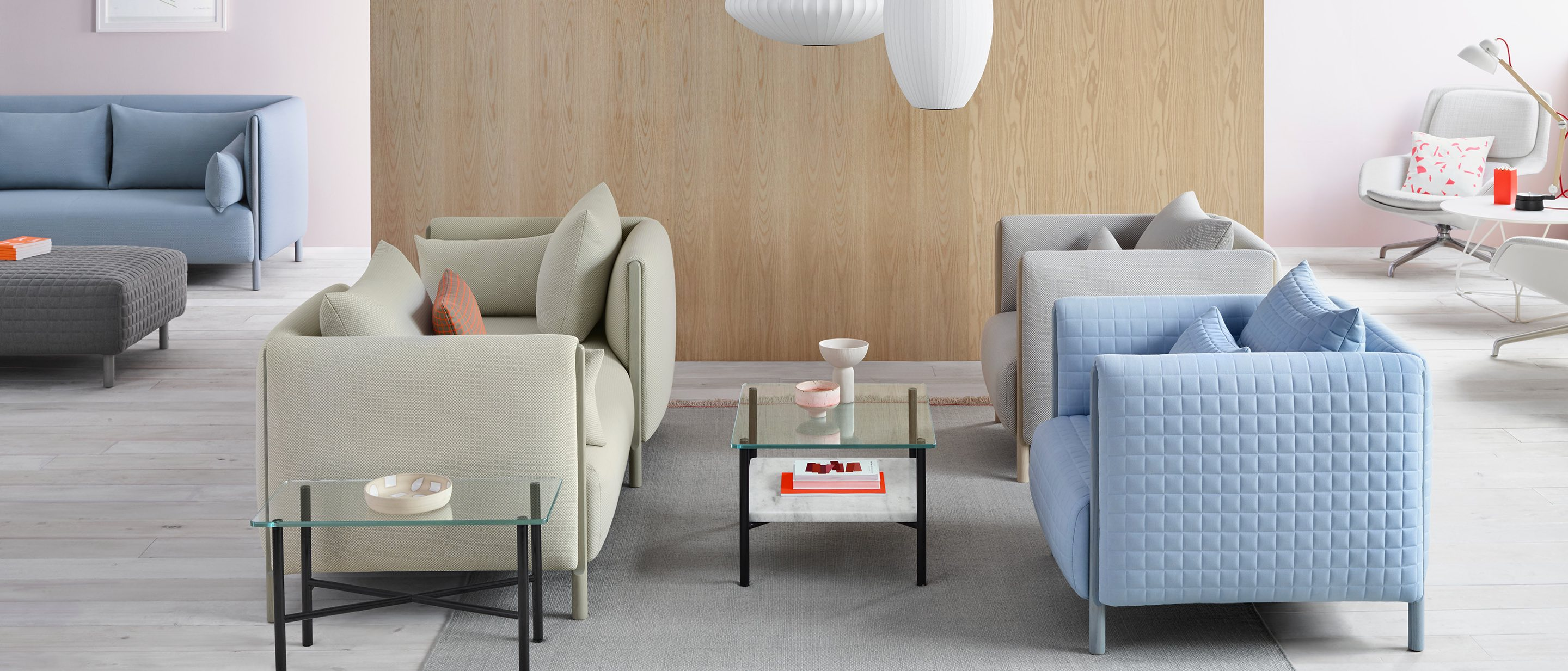 Pastel-colored components from the ColourForm Sofa Group are configured below a trio of Nelson Bubble Lamps to give this lounge area a residential feel.
