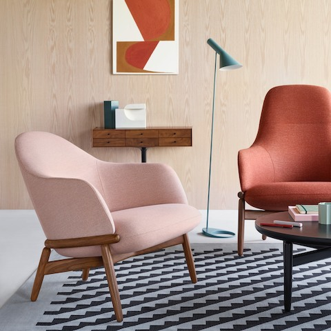 A light pink Reframe Mid-Back Lounge Chair and an orange Reframe High-Back Lounge Chair in a conversational arrangement.