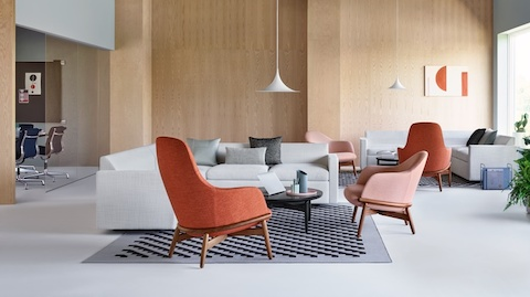 A relaxed lounge setting with Reframe Lounge Chairs in the foreground. A Bevel Sofa sits on a patterned rug in the background.