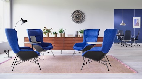 Four blue Striad Lounge Chairs faced toward each other to encourage discussion. The chairs sit on a pink rug and two Striad Tables between them offer complimentary table space. Two Nelson Thin Edge Chests rest in the background.