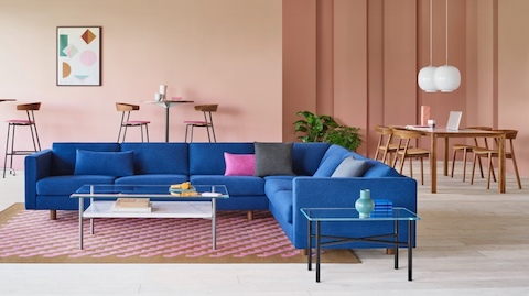 A spacious lounge space featuring a blue Lispenard Sofa accompanied by a Layer Table. The background features a host of Leeway Chairs and Stools.