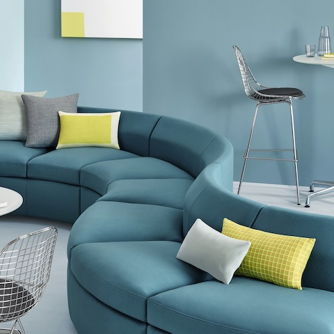 A curved installation of teal Bevel Sofa Group components is used to divide space.