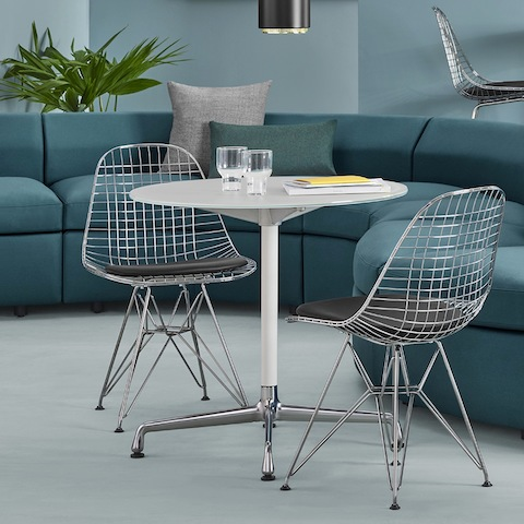 A casual meeting space featuring two Eames Wire Chairs and an Eames Table. The background features Bevel Sofa Group components.