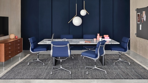 A blue themed meeting space featuring the Axon Table and six Eames Soft Pad Chairs.