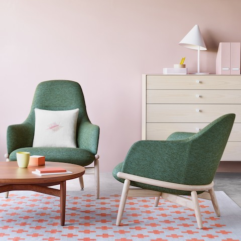 Two green Reframe Lounge chairs gathered beside a walnut Reframe table. The scene is set infront of a pink wall featuring a chest of drawers.