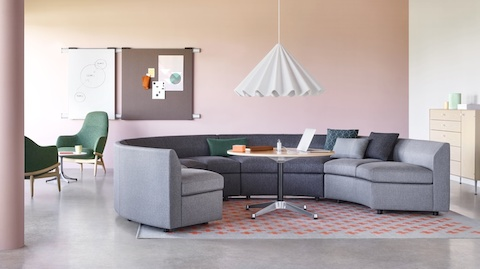 A Bevel Sofa in a circular configuration around an Eames Table. Two green Reframe Lounge Chairs sit casually in the background.