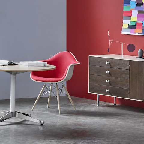 An Eames Molded Fiberglass armchair at a small Eames Table, accompanied by a Nelson Thin Edge Buffet.